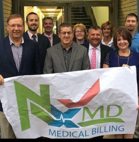 Photo provided A ribbon-cutting is held at NXMD, a medical billing firm offering services to practitioners in the Ohio Valley. Pictured from front left are Brian Schambach and Mike Smith, owners, with Belmont County Commissioner Mark Thomas and Charlene Moffo of Mark H. Kennedy Park. In the back row are, from left, Commissioners J.P. Dutton and Josh Meyer; Carol Barlow, a member of the St. Clairsville Area Chamber of Commerce; Pam Rine, chamber of commerce staff; and A.J. Smith representing Hull & Associates.