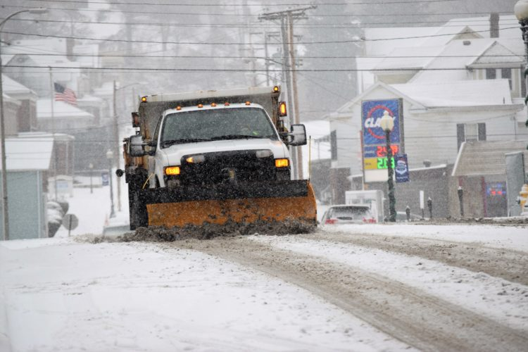 T-L Photo/SHELLEY HANSON/ A city of Martins Ferry truck plows heavy, wet snow off of Hanover Street this morning.