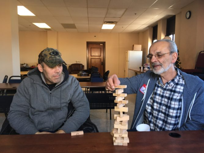 Photo by Casey Junkins Jay Smith, 45, at left, is paralyzed from the chest down and is now homeless. He has been spending nights at the Youth Services System Winter Freeze Shelter. Here, at the shelter, he plays a game of Jenga with YSS CEO John Moses.