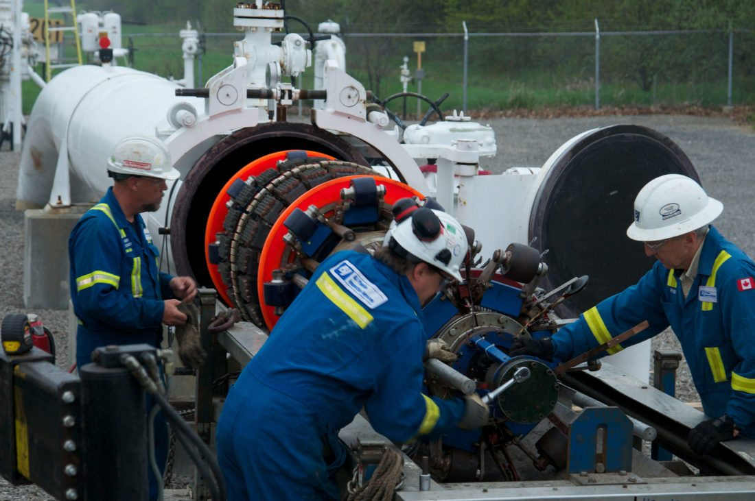 """Natural gas industry workers clean residue from a pipeline through the process known as """"pigging."""" This week, TransCanada placed the $1.6 billion Leach XPress pipeline into service.    Photo Provided"""