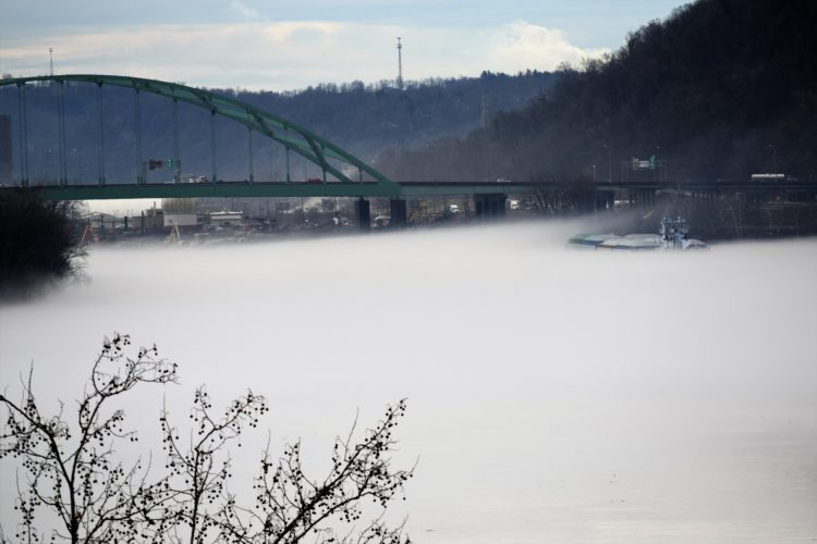 T-L Photo/SHELLEY HANSON A BOAT with barges attached can hardly be seen through the thick fog blanketing the Ohio River on Friday afternoon. This is the Ohio side of the river near Bellaire, taken from the Wheeling Suspension Bridge. The green Interstate 470 bridge is in the background.