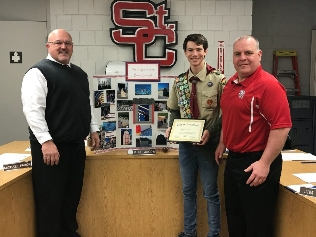 Photo Provided ST. CLAIRSVILLE Superintendent Walt Skaggs, left, and school board President Michael Jacob, right, congratulate Noah Brown on completion of his Eagle Scout project, a storage building for the district.