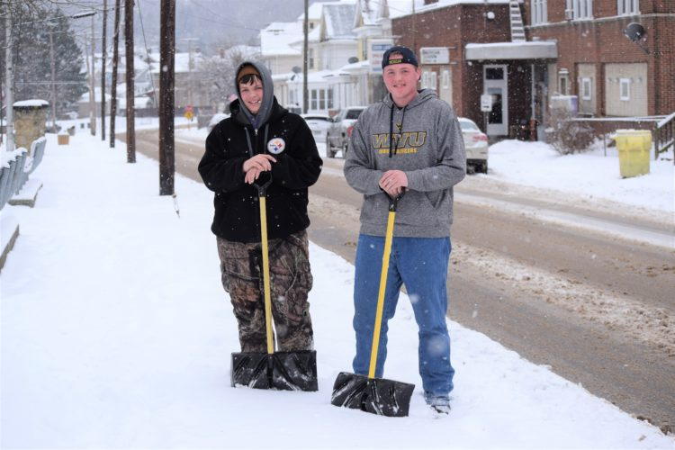 T-L Photo/SHELLEY HANSON MARTINS FERRY residents Dylan Hans, left, and Ringo Blackner, both 16, pause while on the way to their next snow-shoveling job on Tuesday. The Martins Ferry High School students said they have about 10-12 regular customers they shovel for after it snows.