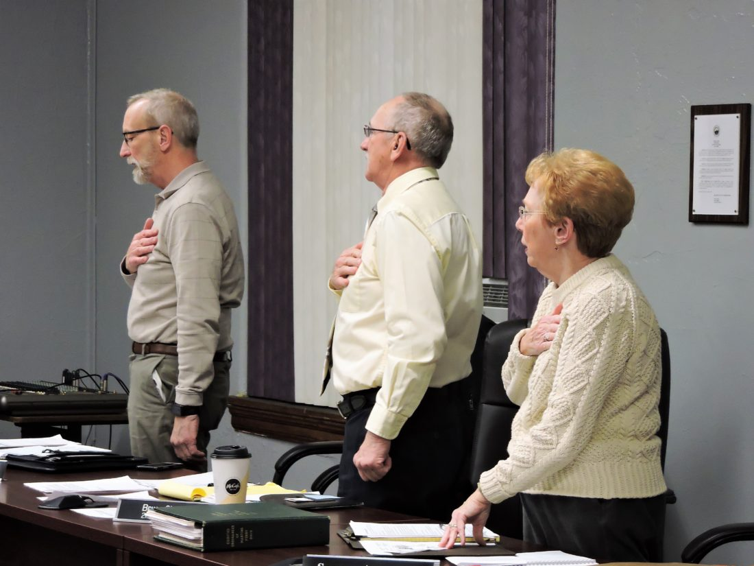 T-L Photo/SHELLEY HANSON MARTINS FERRY City Councilmen Robert Hunker, left, and Bruce Shrodes and Councilwoman Suzanne Armstrong say the Pledge of Allegiance during Wednesday's regular City Council meeting.