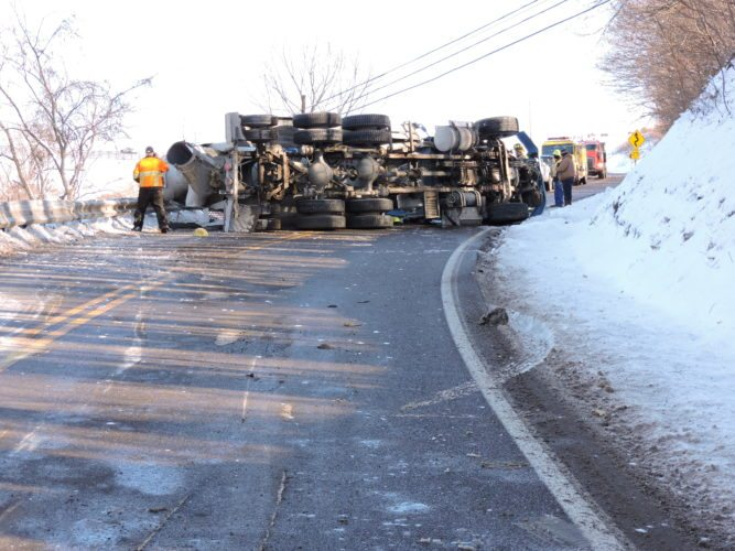 T-L Photo/JENNIFER COMPSTON-STROUGH AN OVERTURNED concrete truck lies across both lanes of Ohio 147 about 2 miles east of Centerville on Thursday afternoon. The driver was taken to Wheeling Hospital for treatment of his injuries, according to Ohio State Highway Patrol troopers.