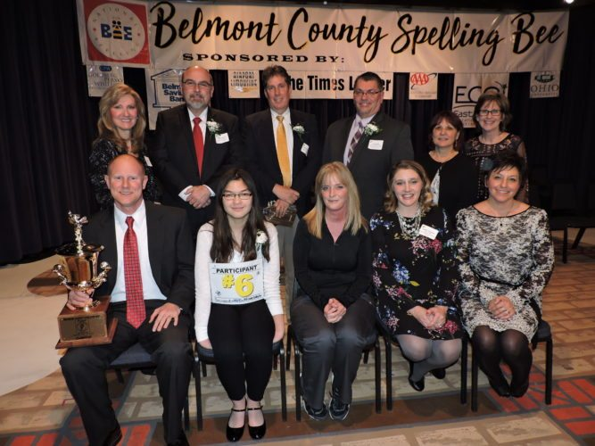 T-L Photo/SHELLEY HANSON BELMONT COUNTY District Spelling Bee sponsors gather with the competition's first-place winner after the event on Thursday at Ohio University Eastern in St. Clairsville. Front row, from left, are Mike McKeever, St. Clairsville Middle School principal, who is holding the bee's Traveling Trophy to be displayed at the school; bee winner Linh Le, an eighth grader at St. Clairsville, and her mother Katy Le; Amber Toriseva and Lori Robson both of the East Central Ohio Educational Service. Back row, from left, Lisa Stupak of East Central Ohio Educational Service, Richard Silverio and Mark Nicholson of Belmont Savings Bank; Joe Lovell of The Times Leader; and Beth Rushton and Carol Henderson, both bee coordinators and fifth grade teachers. Le will compete in the Scripps National Spelling Bee in Washington, D.C., from May 27-June 1.