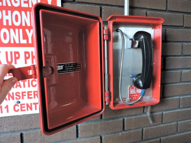 T-L Photo/SHELLEY HANSON THE RED emergency 911 call box at the Bellaire Police Department has been moved indoors, just inside the first set of double doors at the station on Belmont Street. The station also will now be unlocked for visitors when an officer is at the station.