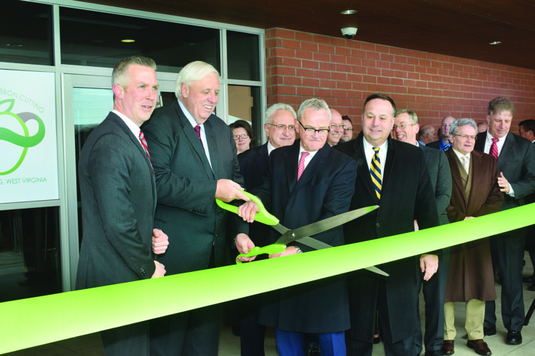 Photo by Scott McCloskey Cutting the ribbon to officially open the headquarters of The Health Plan in downtown Wheeling on Friday, from left, Wheeling Mayor Glenn Elliott, Gov. Jim Justice, company CEO Jim Pennington and former mayor Andy McKenzie.