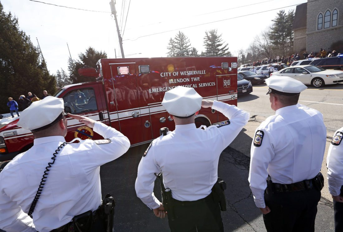Columbus Police honor guard members salute the ambulance carrying the body of Westerville Police officer Eric Joering during a procession transporting the bodies of Joering and Anthony Morelli from the Franklin County Coroners Office to the Hill and Morel