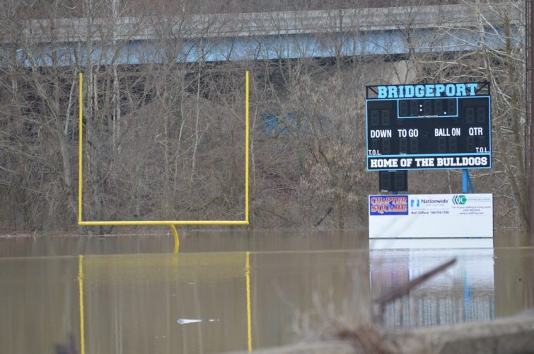 SEVERAL FEET of creek water floods the Bridgeport High School football complex off National Road in Brookside on Saturday.