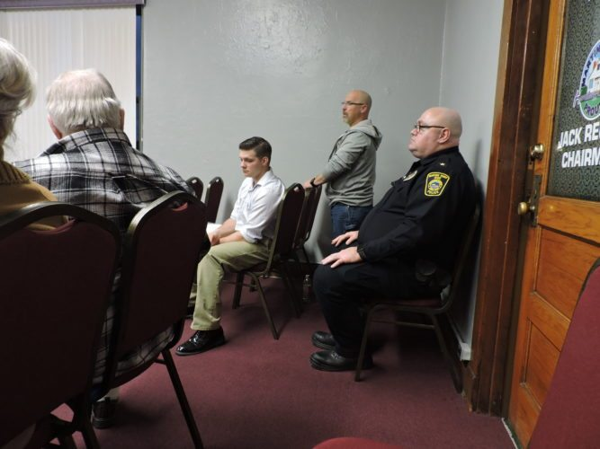 T-L Photo/SHELLEY HANSON/ POLICE CHIEF John McFarland, at far right, listens during Wednesdayás regular meeting. Also shown is Pearl Street resident Robert George sitting in front of the chief and Water Superintendent Bill Suto, center, gives his report.