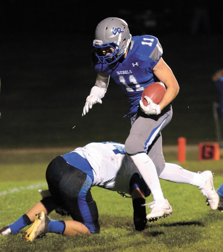 T-R PHOTO BY ROSS THEDE • Gladbrook-Reinbeck's Erik Knaack (11) eludes Montezuma defender Zach Henry on his way to scoring an 18-yard touchdown reception in the third quarter. The Rebels won 35-0 and advanced to the UNI-Dome for the third-straight year.