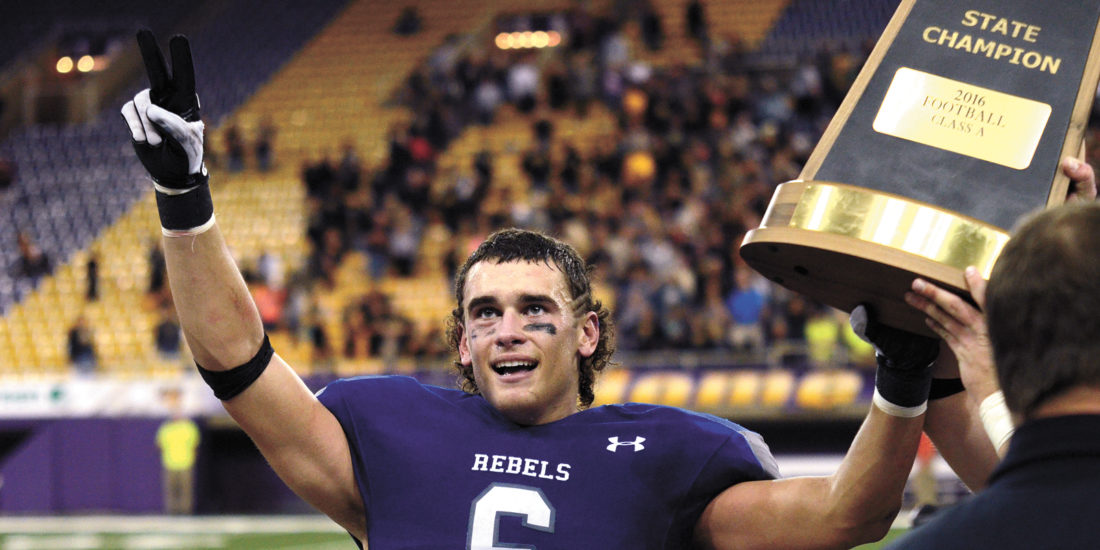 T-R PHOTO BY STEPHEN KOENIGSFELD • Parker Bown celebrates by  raising his hand and the Class A state championship trophy after the Rebels' 20-19 win against Bishop Garrigan on Thursday at the UNI-Dome. The win gave Gladbrook-Reinbeck back-to-back state titles and the first perfect season in school history.