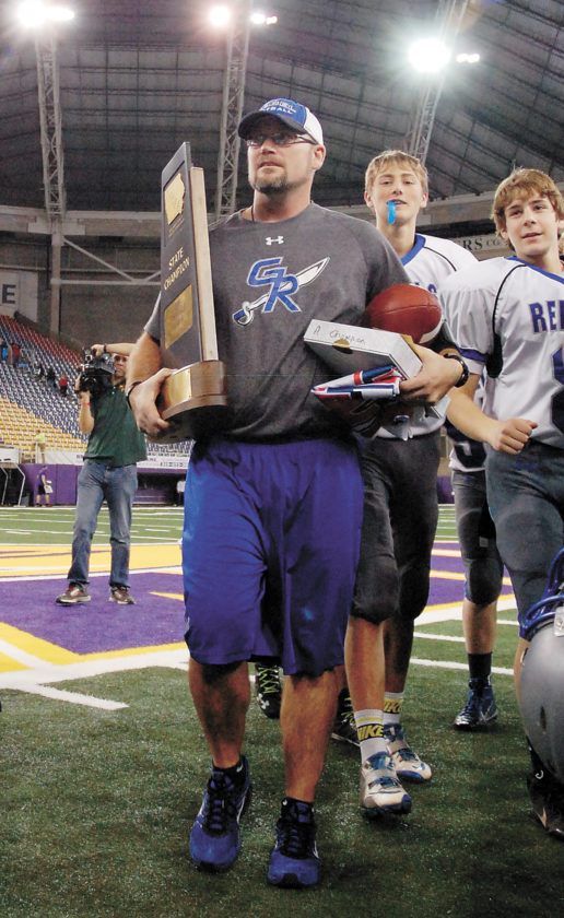 T-R FILE PHOTO • Gladbrook-Reinbeck head football coach John Olson walks off the UNI-Dome turf with the school's first of two consecutive Class A state championship trophies after his Rebels defeated Akron-Westfield 52-20 on Nov. 19, 2015, in Cedar Falls. A year later, G-R defeated Bishop Garrigan 20-19 to successfully defend that title.