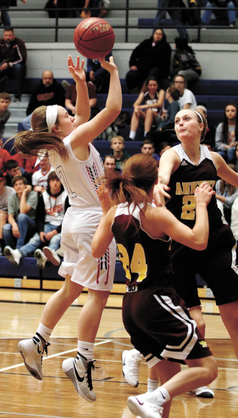 T-R PHOTO BY ADAM RING • Marshalltown's Alyvia Chadderdon, left, gets off a jumpshot in the second half against Ankeny Friday night at the Roundhouse. The visiting Hawkettes downed the Bobcats 65-24.