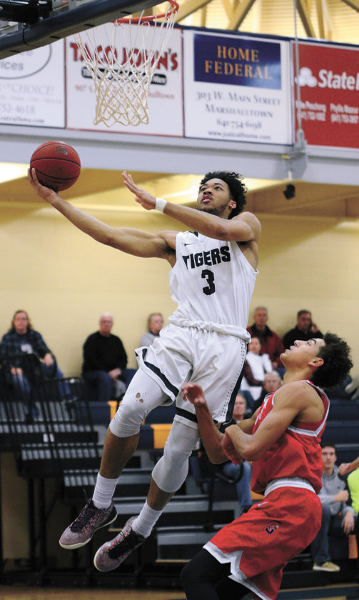 T-R PHOTO BY STEPHEN KOENIGSFELD • Marshalltown Community College's Jamir Coleman (3) takes a fast break layup past KeShawn Wilson during the first half of Wednesday's game against Southwestern. Coleman had 15 points off the bench as the Tigers fell 94-80.