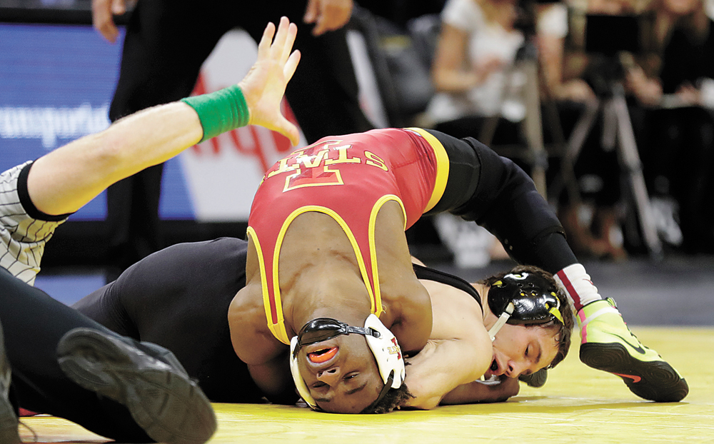AP PHOTO • Iowa's Thomas Gilman, right, scores near-fall points against Iowa State's Markus Simmons during their 125-pound match in a college wrestling meet Saturday at Carver-Hawkeye Arena in Iowa City. The third-ranked Hawkeyes won 26-9.