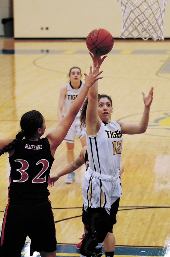 T-R PHOTO BY ADAM RING • Marshalltown Community College's Dalia Cantu (12) gets a shot off against Southeastern CC's Ciera Walker (32) during the second quarter Monday at the Student Activity Center. MCC won 59-53, winning its fifth game of the year to surpass last year's win total.