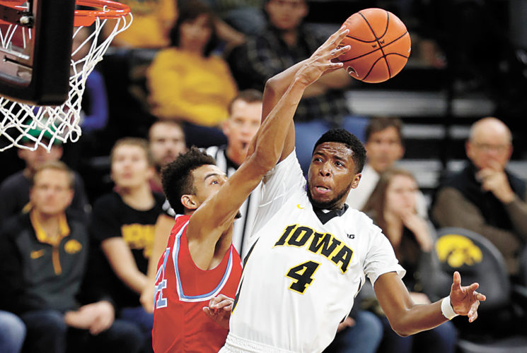 AP PHOTO • Iowa guard Isaiah Moss (4) is fouled by Delaware State forward DeVaughn Mallory while driving to the basket during the second half of a men's college basketball game Thursday in Iowa City.