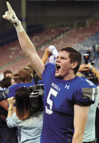 T-R PHOTO BY STEPHEN KOENIGSFELD • Gladbrook-Reinbeck senior Matt Roeding (5) celebrates the Rebel football team's second-straight Class A state championship after a 20-19 win against Bishop Garrigan in the Nov. 17 title game at the UNI-Dome in Cedar Falls.