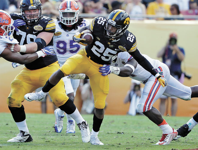 AP PHOTO • Iowa running back Akrum Wadley (25) eludes Florida linebacker Vosean Joseph on a run during the first half of the Outback Bowl on Monday in Tampa, Fla.