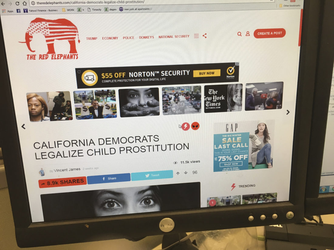 AP PHOTO In this Jan. 19, photo, a fake news story is positioned near ads from major global corporations on The Red Elephants website.