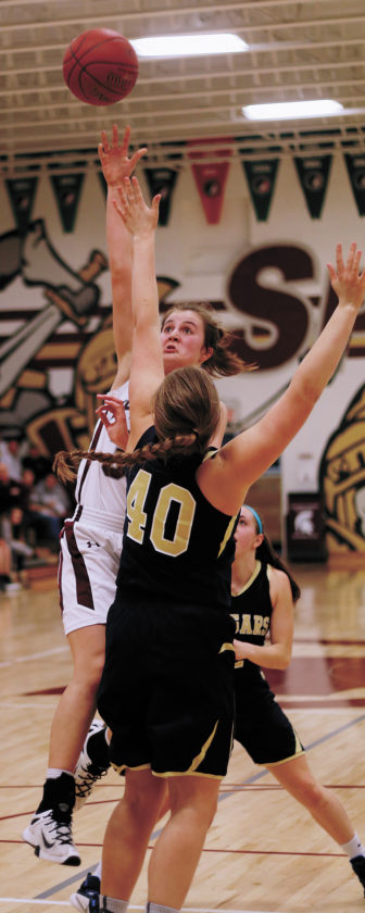 t-r photo by  Grundy Center's Kylie Willis puts up a shot over Sumner-Fredericksburg's Georgia Ackley (40) in the third quarter of Tuesday's Class 2A Region 5 Quarterfinal in Grundy Center. Grundy Center came from behind to win 65-59 in double-overtime to advance to Friday's semifinal.