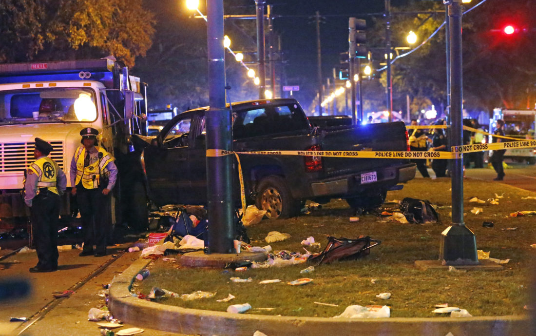 AP PHOTO Police stand next to a pickup truck that slammed into a crowd and other vehicles, causing multiple injuries, coming to a stop against a dump truck, during the Krewe of Endymion parade in New Orleans, Saturday.
