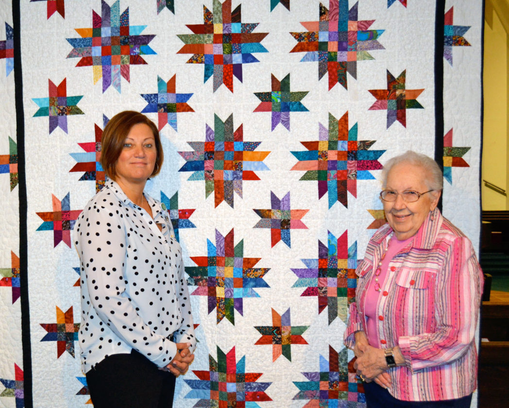 T-R PHOTO BY SARA JORDAN-HEINTZ Trinity Lutheran Church is raffling off this quilt made by congregant Dorothy Williamson, right, from now until April 23. But what makes this quilt special, is it's the second time it has been raffled off; the first time was back in 2000. However, the quilt was recently returned by the person who won it, for lack of storage space, and is now being raffled again, with the funds to benefit Community Health Initiative Haiti, an organization in which congregant Kim Riley-Adams, left, volunteers.