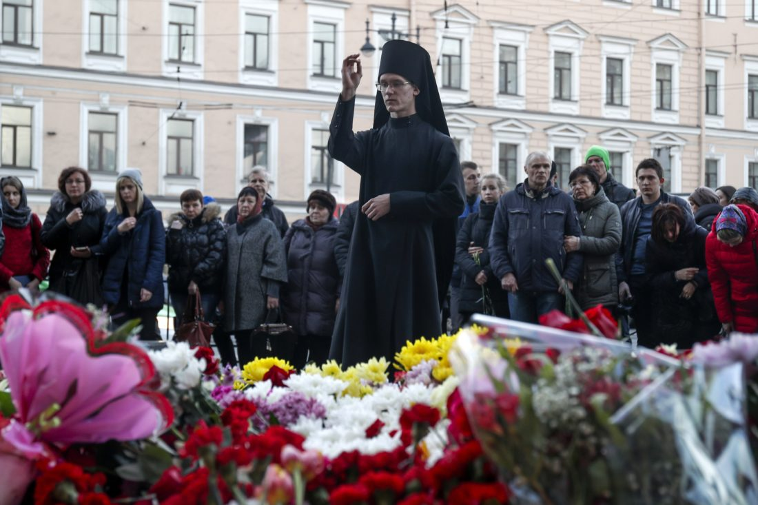 AP PHOTO An Orthodox priest blesses at a symbolic memorial at Technologicheskiy Institute subway station in St. Petersburg, Russia, Tuesday. A bomb blast tore through a subway train deep under Russia's second-largest city St. Petersburg Monday, killing several people and wounding many more in a chaotic scene that left victims sprawled on a smoky platform.