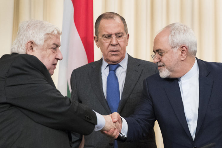 AP PHOTO Russian Foreign Minister Sergey Lavrov, center, stands in the middle as Syrian Foreign Minister Walid Muallem, left, and Iranian Foreign Minister Mohammad Javad Zarif shake hands after a press conference following their talks focused on Syria in Moscow, Russia, Friday.