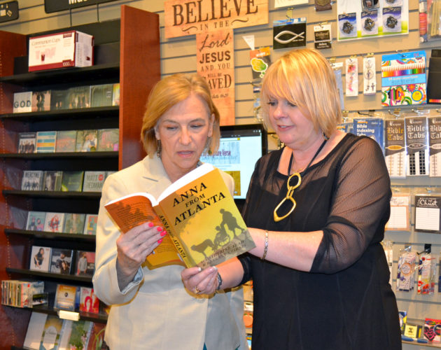"T-R PHOTO BY SARA JORDAN-HEINTZ Tuesday afternoon, authors Catherine Team, left, and Beverly Smirnis, signed copies of their new book ""Anna From Atlanta"" at Stepping Stones Christian Bookstore. The historical fiction novel is set in Marshalltown in the 1930s, based on the real-life tale of a caregiver named Anna who came to Marshalltown to care for a disabled youth."