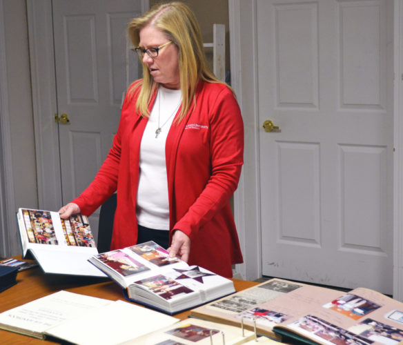 T-R PHOTO BY SARA JORDAN-HEINTZ Amy Pieper, administrator of Marshall County's ISU Extension and Outreach office in Marshalltown, looks through scrapbooks during Wednesday's open house, celebrating the organization's 100th anniversary in the county and Iowa's Land Grant Legacy.