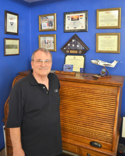 T-R PHOTO BY CHUCK FRIEND CW4 Ron Snyder of Marshalltown is pictured with many of his awards received during and after his retirement from serving as a helicopter pilot for 40 years in the U.S. Army and Iowa National Guard. The small model plane on the desk at right is the type of fixed wing plane he also flew during his time of service.
