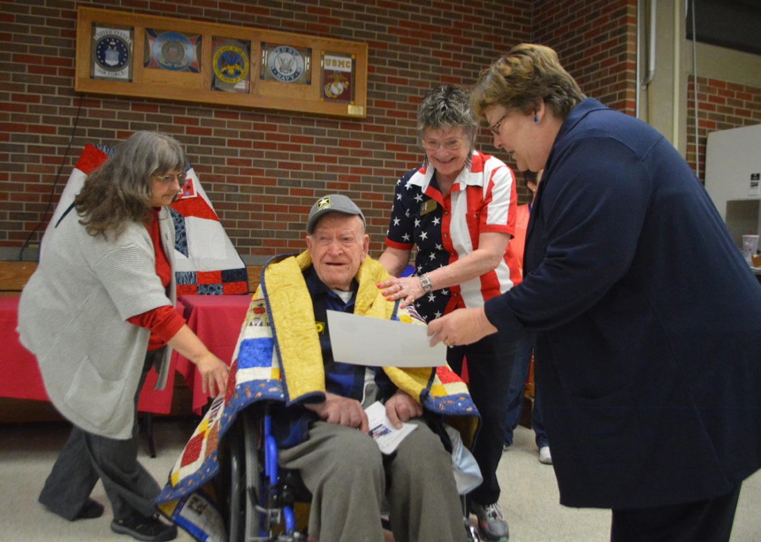 T-R PHOTO BY MIKE DONAHEY  Dale Hall, 94, of the Iowa Veterans Home, is congratulated after receiving a well-earned Quilt of Valor Saturday in the facility's Malloy Leisure Resource Center. Hall and 15 other World War II veterans were honored during the event sponsored by Central Iowa Quilt Sew-ciety.
