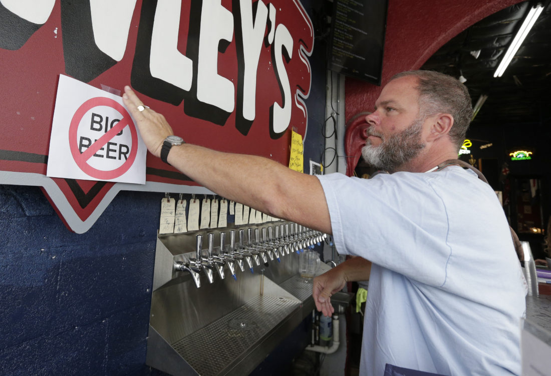 "AP PHOTO Michael Brawley places a ""No Big Beer"" sign behind the bar at Brawley's Beverage in Charlotte, N.C., Thursday. Brawley is among at least a handful of stores or restaurants that announced they don't intend to stock Wicked Weed in the future."