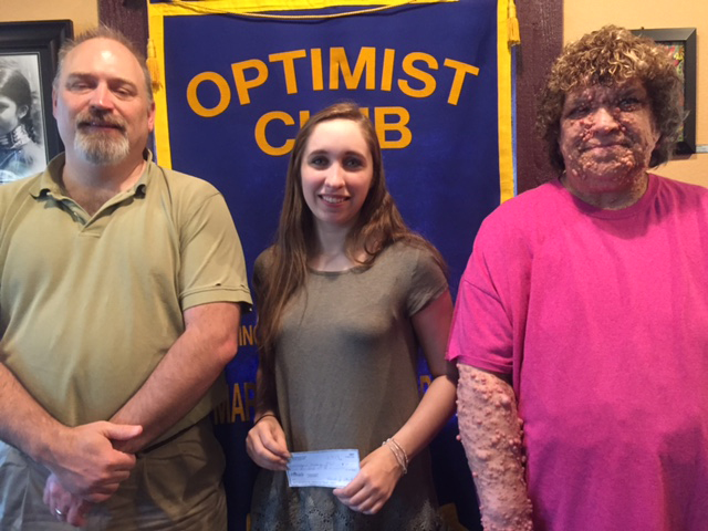 CONTRIBUTED PHOTO Megan Messina, center, accepts the Tom Stanley Memorial Scholarship from the Morning Optimist Club at the Tuesday club meeting. Todd Stanley and Wendi Stanley, children of the deceased Tom Stanley, for whom the scholarship was named, congratulate Messina. Messina is a senior at West Marshall High School who plans to attend Iowa State University in the fall.