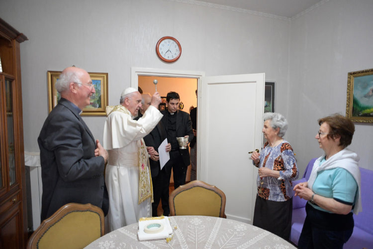AP PHOTO Pope Francis blesses an home during a visit to a popular neighborhood in Ostia, near Roma, where he made a surprise visit along with local priest, stopping in various homes to bless the families living there, Friday.