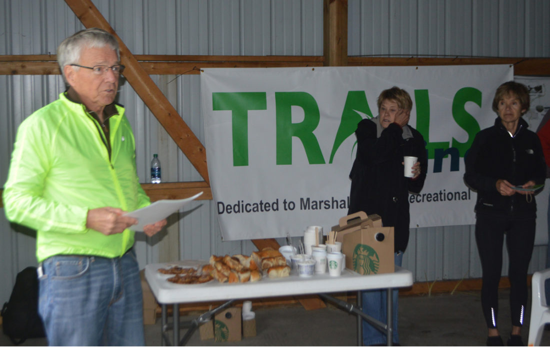 T-R PHOTO BY MIKE DONAHEY  Terry Briggs of Marshalltown, far left, president of TRAILS, Inc., speaks before a group of local elected officials, business representatives and a host of Iowa River Trail supporters at Friday's Bike to Work Day. A steady rain and cold temperatures required event organizers to gather inside a Trails, Inc. building on Wilson Circle. Briggs and Kim Schryver also of TRAILS, Inc., briefed the group on construction progress of the Marshall County portion of the 34-mile recreational trial which, when completed, will connect Marshalltown with Steamboat Rock.