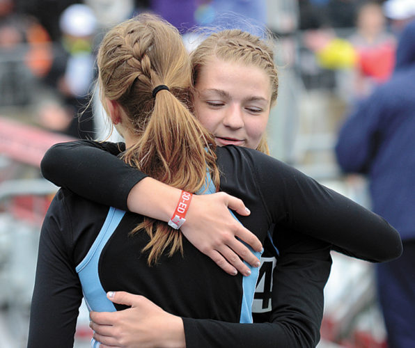 T-R PHOTO BY STEPHEN KOENIGSFELD • South Tama County twin sisters Allison, right, and Lauren Yuska share a hug at the completion of their final high school race. The Trojans' sprint medley relay team of Shae Slaven, Ashton Graham and the Yuska sisters placed 19th in Class 3A in a time of 1 minute, 54.44 seconds on Saturday at the state meet in Des Moines.