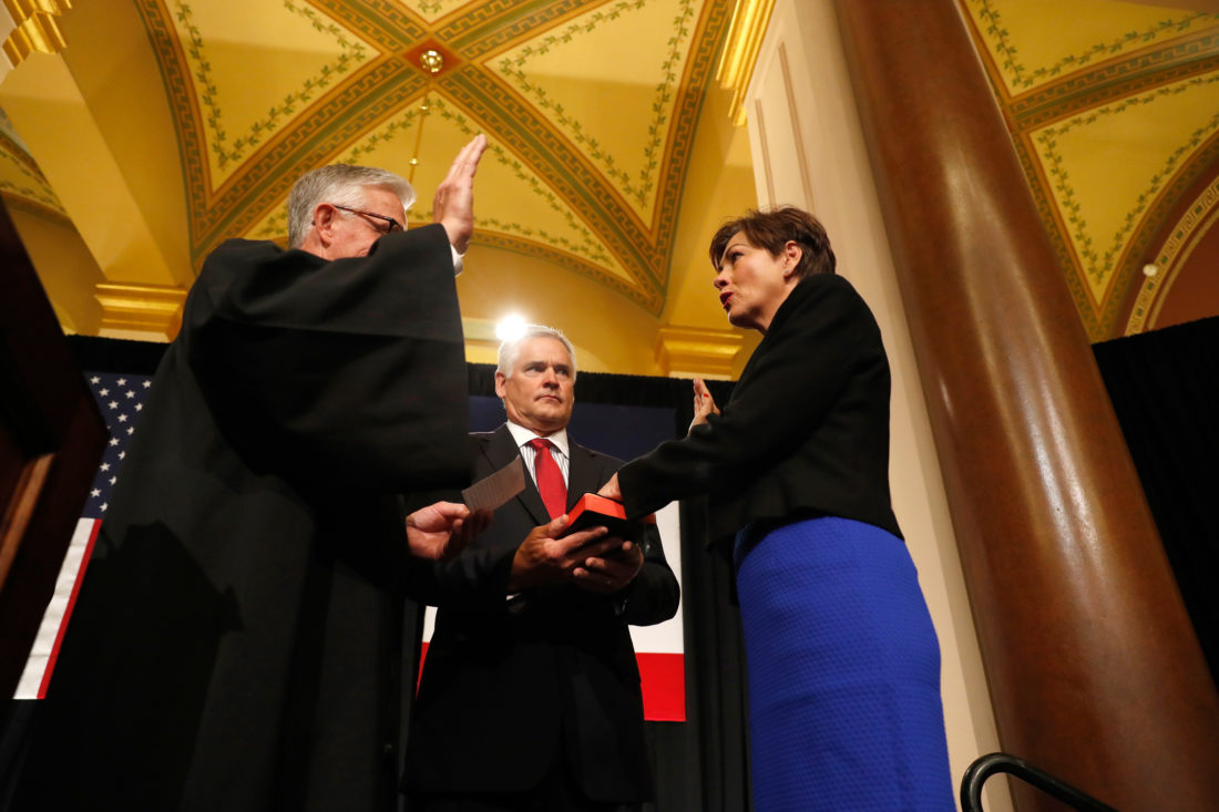 AP PHOTO Iowa Lt. Gov. Kim Reynolds, right, is sworn in as governor by Iowa Supreme Court Chief Justice Mark Cady during a ceremonial swearing in Wednesday at the Statehouse in Des Moines Holding the bible is her husband Kevin Reynolds.