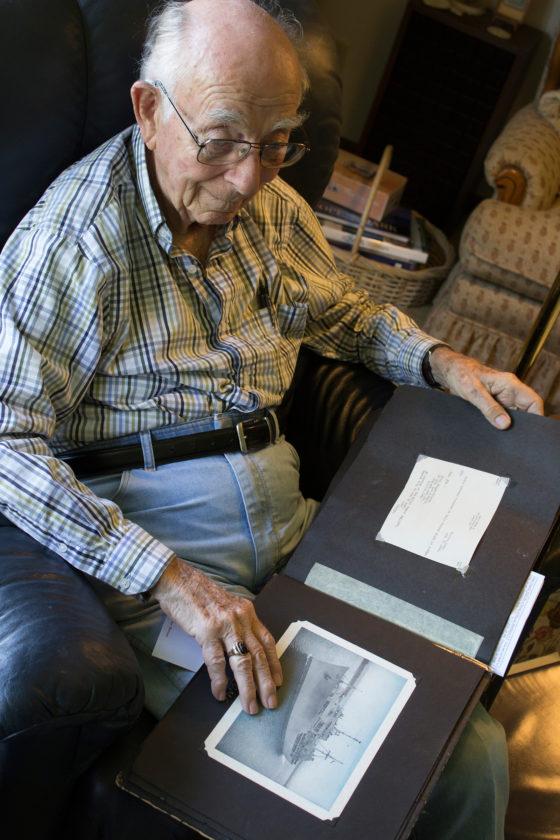 T-R PHOTO BY MIKE BURVEE World War II veteran George Taylor  reviews a scrapbook of military memories.