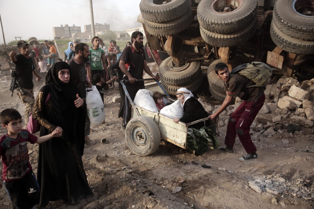 AP PHOTO In this May 10 file photo, an elderly woman and a child are pulled on a cart as civilians flee heavy fighting between Islamic State militants and Iraqi special forces in western Mosul, Iraq.