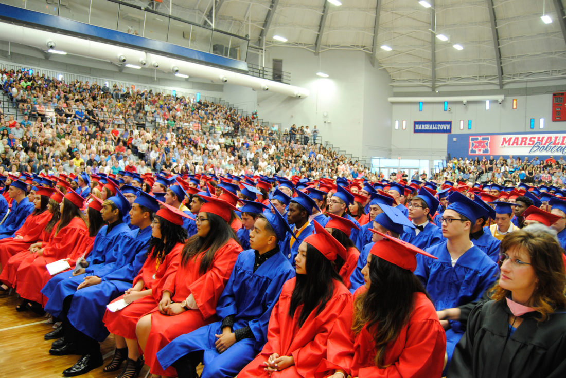 T-R PHOTO BY ADAM SODDERS Girls dressed in red caps and gowns while boys wore blue in front of a packed Marshalltown High School Roundhouse Sunday afternoon.
