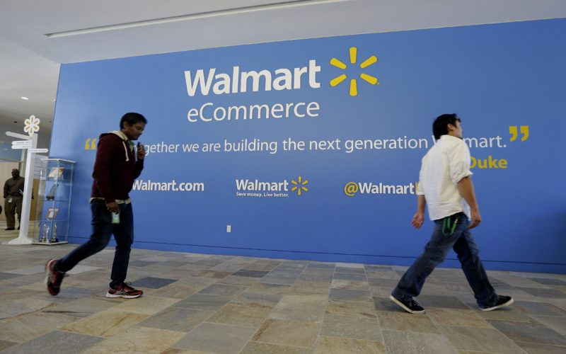 AP PHOTO In this Sept. 18, 2013, file photo, two Wal-Mart employees walk past a sign in the lobby at the Walmart.com office in San Bruno, Calif. Wal-Mart's acquisition of Jet.com is accelerating its progress in e-commerce as it works to narrow the gap between itself and online leader Amazon. Wal-Mart is betting its online future on essentials like produce and groceries and has adjusted its shipping strategy. But Amazon keeps innovating too.