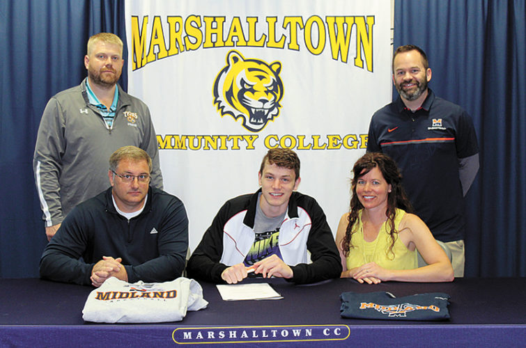 PHOTO PROVIDED • Marshalltown Community College graduate Reggie Gradwell, center, is seated alongside his parents, Jim and Wendy Gradwell, while signing his National Letter of Intent to continue his basketball career at Midland University. Joining Gradwell for the signing ceremony was MCC head coach Brynjar Brynjarsson, standing at left, and Midland head coach Oliver Drake.