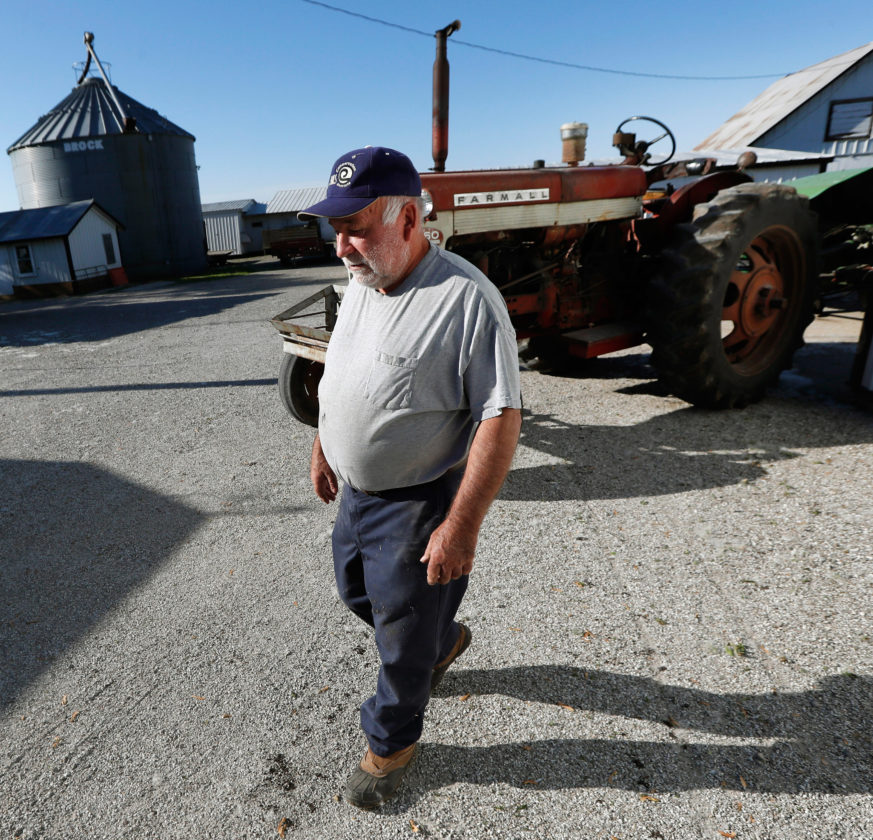 AP PHOTO In this Thursday photo, Chris Petersen walks past a tractor on his farm,  in Clear Lake. Farm groups and some members of Congress from farm states are decrying proposed cuts to crop insurance and other safety net programs for farmers included in President Donald Trump's budget.