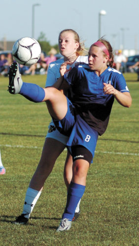 T-R PHOTO BY ROSS THEDE • Grundy Center/Gladbrook-Reinbeck sophomore midfielder Sydney Mathews (8) attempts to play the ball back over her head while being pressured by Nevada's Mikayla Long during the first half of Monday's Class 1A Region 4 final in Nevada. The fifth-ranked host Cubs defeated the Rebels, 4-0, to advance to the state tournament for the sixth year in a row.