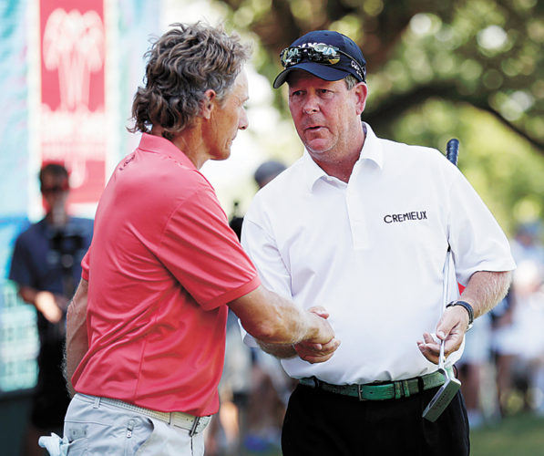 AP PHOTO • Glen Day, right, is greeted by Bernhard Langer after his birdie putt on the 18th green during the second round of the Principal Charity Classic golf tournament Saturday in Des Moines.