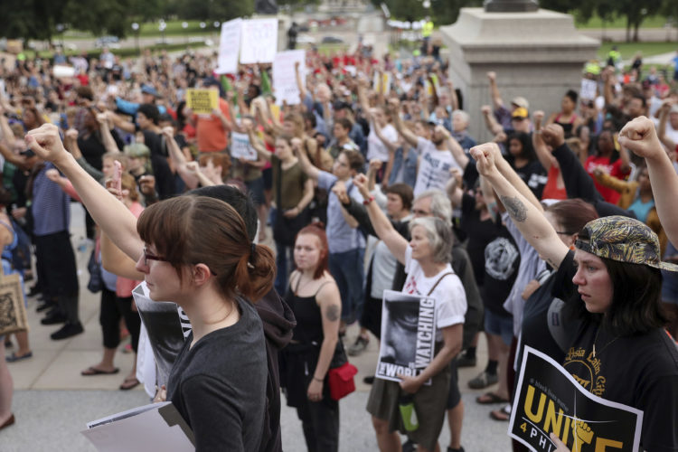 AP PHOTO Supporters of Philando Castile hold their fists up in solidarity during a gathering Friday, outside the state Capitol in St. Paul, Minn. The vigil was held after St. Anthony police Officer Jeronimo Yanez was cleared Friday in the fatal shooting of Castile last year.